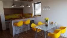 Žlutá kuchyně - horní dvířka jsou vyrobena ze světle šedého perlového lamina v kombinaci s ořechem H3734, pracovní deska také ořech H3734 a k tomu žluté grafosklo.